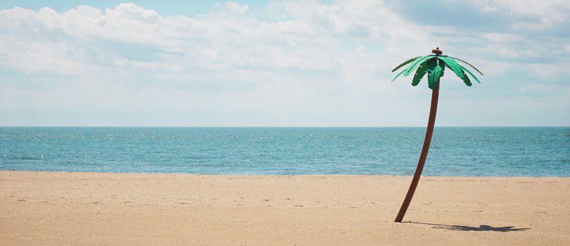 Imagen ornamental: palmera de plástico que parece de verdad sobre la arena de una playa