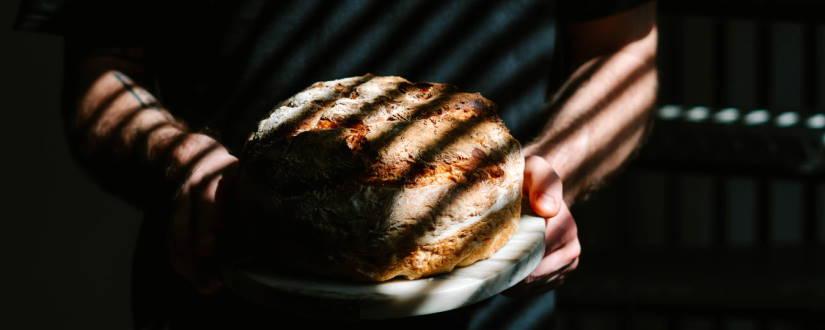 Imagen ornamental, una persona llevando un pan que ha hecho con sus manos. Foto por Toa Heftiba, CC0