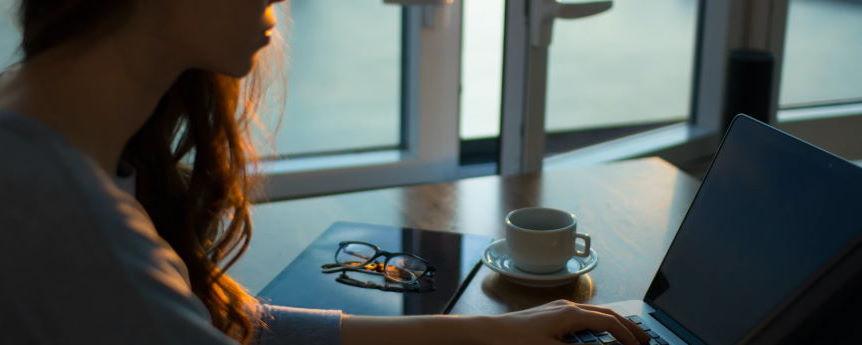 Imagen ornamental. Una mujer trabajando con un ordenador frente a una ventana abierta.
